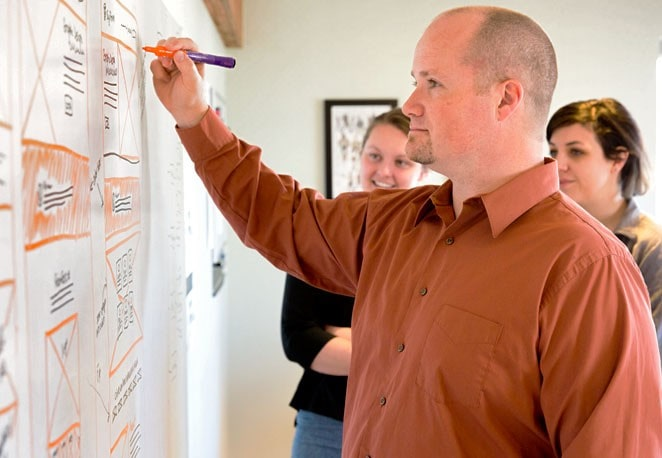Drew Schug showing clients wireframing for website redesign