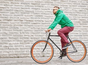 Man riding pedal bike down sidewalk