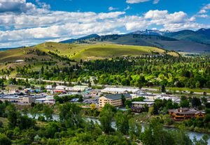 view of green and lush downtown Missoula, Montana from the top of a hill during the summertime