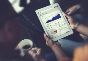 woman holding an ipad looking at analytics information and graphs surrounded by two other people looking at the data