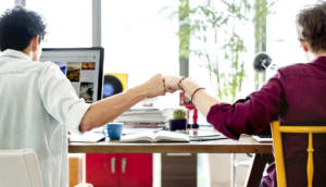 two men in a business office fist bumping