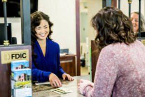 woman teller distributes money